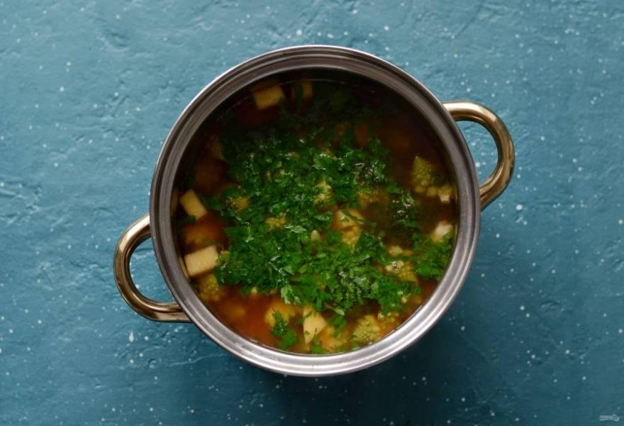 Добавьте специи, соль и рубленую зелень. Проварите суп еще 1 минуту и снимите с огня.