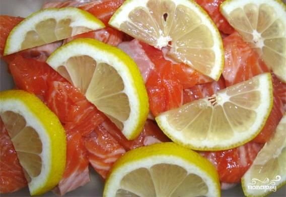 Лимон промойте, нарежьте тонкими дольками. Добавьте их к рыбе.