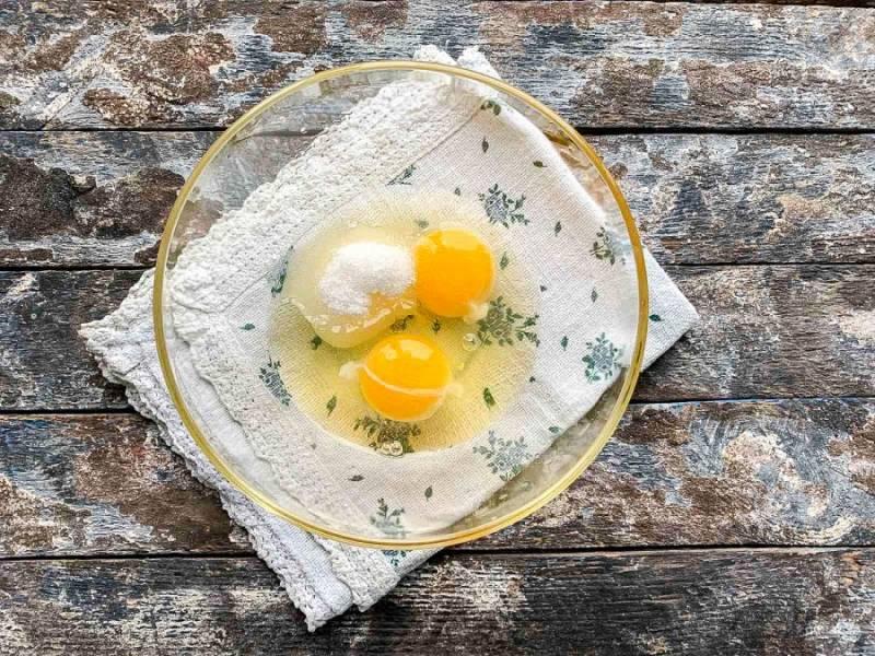 В глубокую тарелку вбейте яйца, добавьте сахар и взбейте.