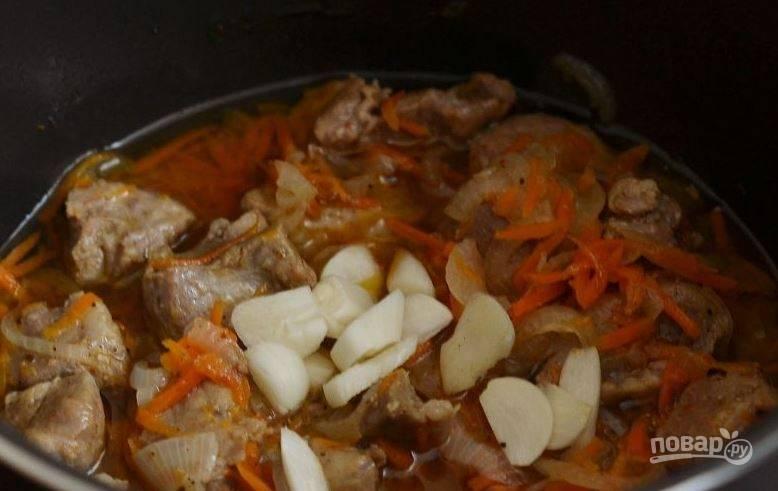 Овощи томите в режиме выпечки десять минут. Затем очистите чеснок и выложите зубчики в плов.