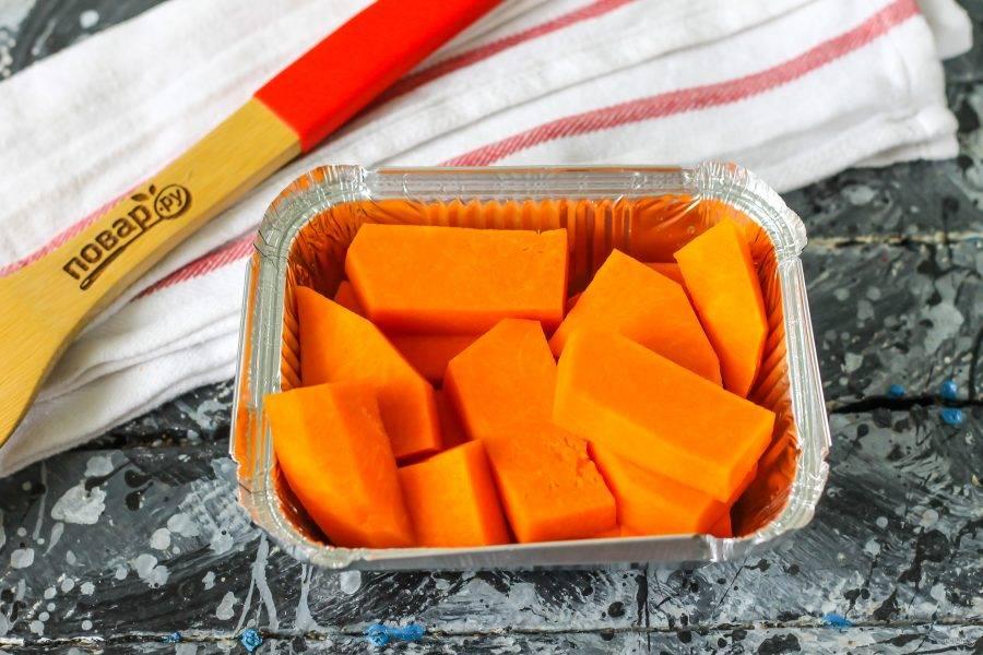 Очистите тыкву от кожуры, промойте и нарежьте средними кубиками, ломтиками. Выложите в форму для запекания. Тыква должна быть снизу, чтобы она впитывала в себя сок запеченных абрикосов.