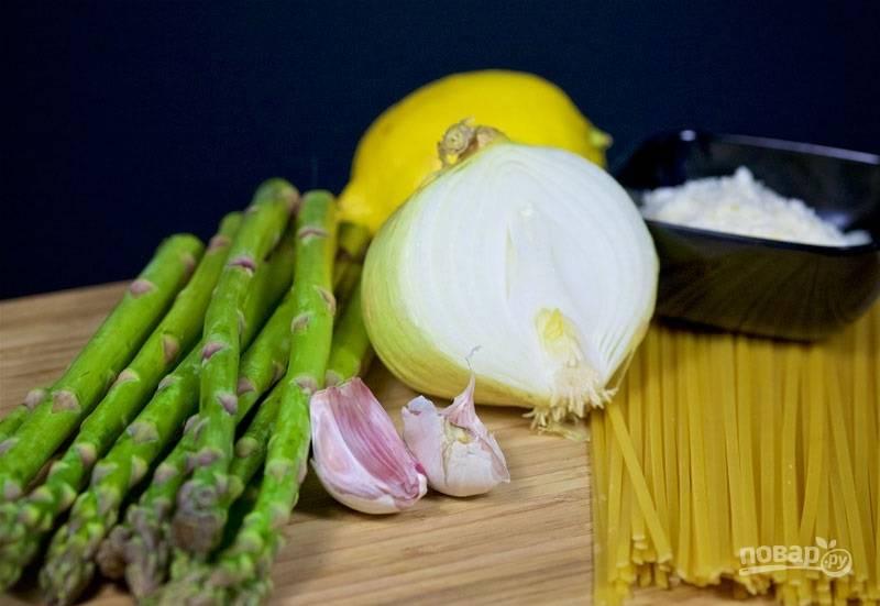 1. Первым делом налейте воду в кастрюлю и поставьте на огонь. Спаржу вымойте, обсушите и нарежьте. Натрите на терке сыр и цедру лимона.