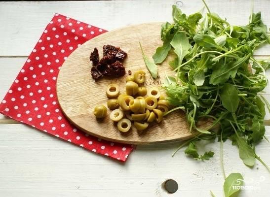 Рукколу вымойте и порвите руками. Томаты разрежьте на небольшие кусочки, а оливки порежьте кусочками.