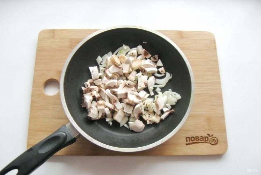 Репчатый лук и грибы мелко нарежьте и выложите в другую сковороду. У меня были шампиньоны.