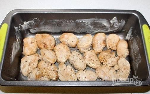 Форму для выпечки смажьте сливочным маслом. На дно уложите кусочки курицы. Посолите их и поперчите.
