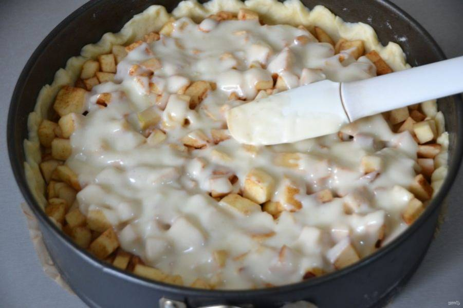 Выложите сверху на яблоки заливку, разогрейте духовку до 180 градусов. Поставьте пирог в духовку на 50 минут.