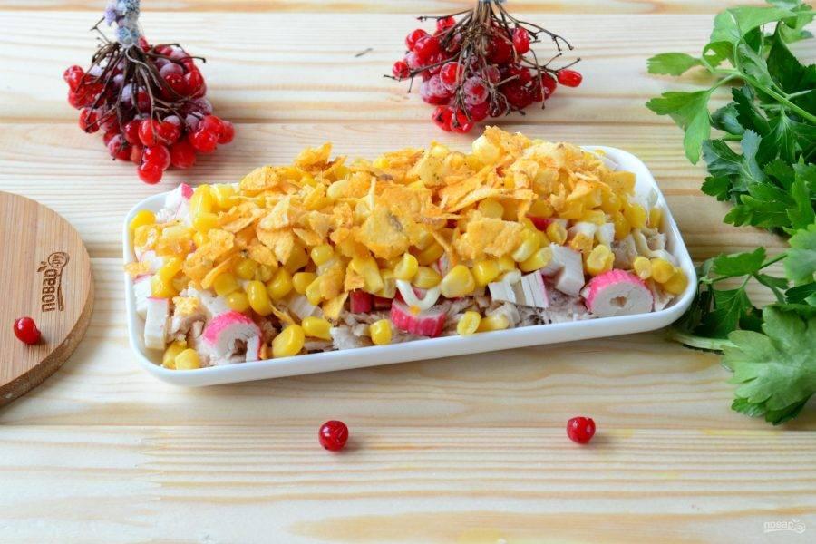 Далее идут желтые ингредиенты. Сначала выложите кукурузу (предварительно из нее нужно сцедить весь сок), а следом – измельченные чипсы. Снова смажьте майонезом.