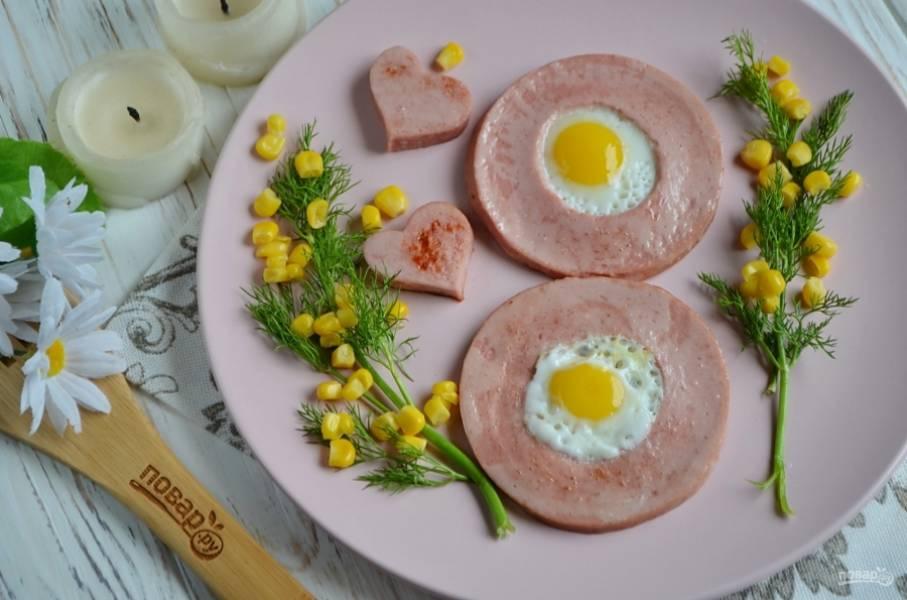 Осторожно лопаткой снимите яичницу. Украсьте веточками укропа, кукурузой, имитируя цветение мимозы. Приятного!