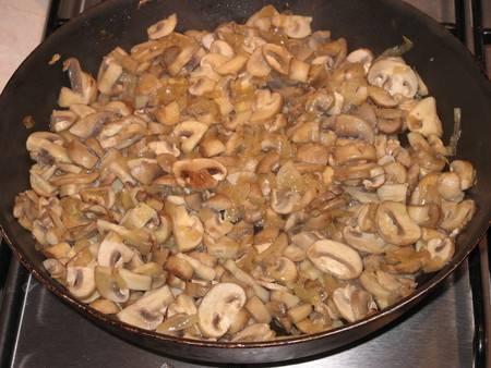 Выкладываем к луку грибы, продолжаем жарить все вместе, пока из шампиньонов не выпарится лишняя влага.