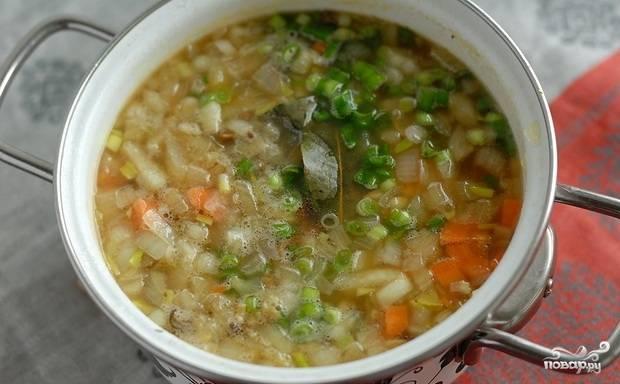 Теперь процеживаем куриный бульон и добавляем в него перловую крупу, варим в течение 40 минут. Затем добавляем грибы, можно вместе с водой, и варим все еще 10-15 минут. Добавляем нарезанные морковь и репчатый лук, лавровый лист, солим и перчим, даем провариться 5-7 минут. В последнюю очередь всыпаем зеленый лук, доводим суп до кипения и выключаем.