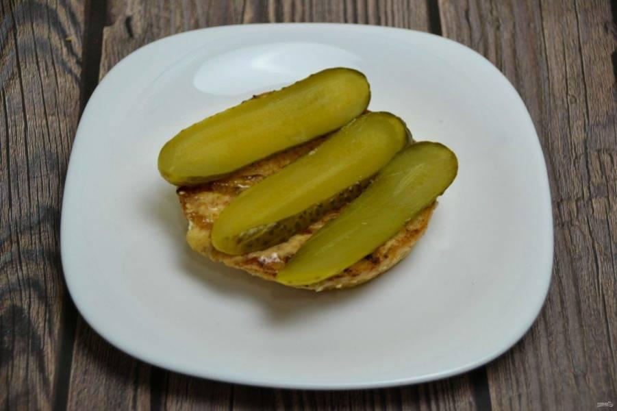 Сборку сырного бургера производите следующим образом, на нижнюю часть булочки выложите порезанный на ломтики консервированный или маринованный огурец.