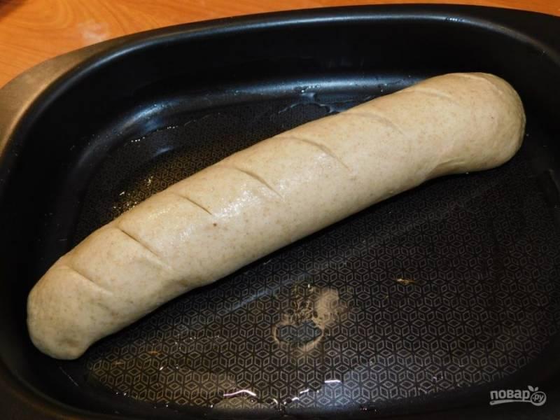 Сделайте надрезы и подверните края. Смажьте маслом сам хлеб и форму, на которой он будет выпекаться. Дайте ему подойти еще минут 30 и поставьте в духовку при температуре 180 градусов на 40 минут.