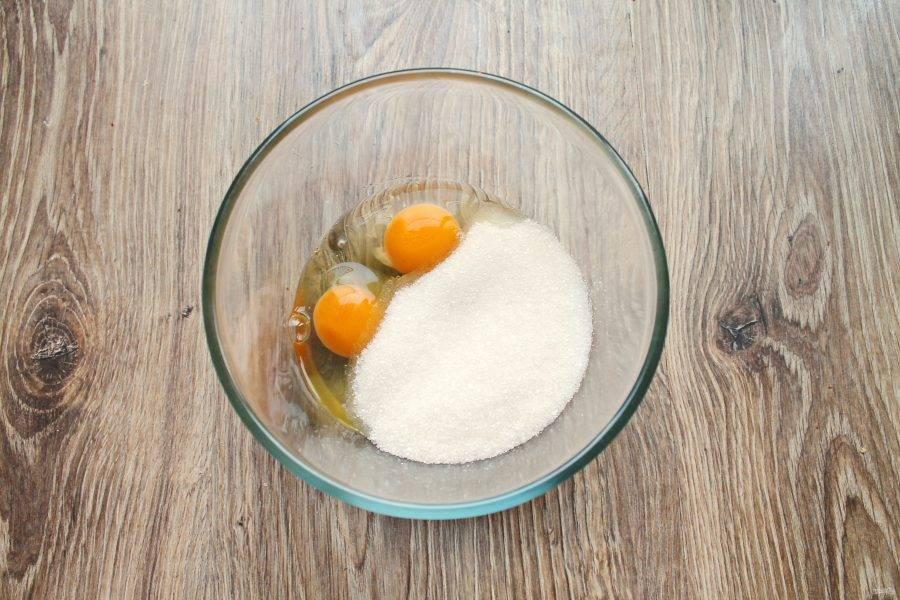 В глубокую миску разбейте яйца, и всыпьте сахар. Все взбейте миксером до пышной массы.