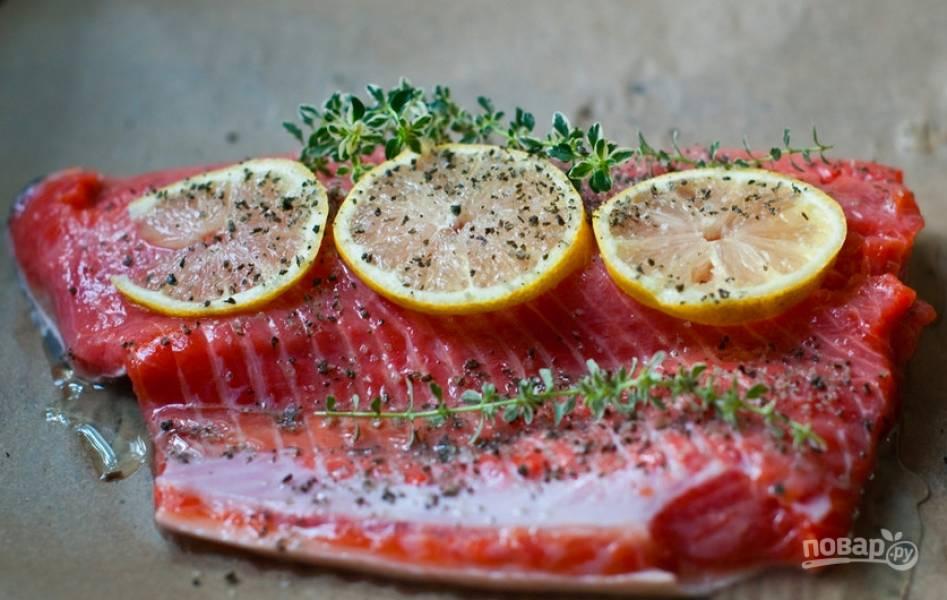 Вымойте и просушите филе рыбы, выложите его на пергаментную бумагу кожей вниз. Лимон нарежьте тонкими дольками, сбрызните соком рыбу и выложите пару долек сверху, присыпьте сушеным розмарином, положите свежие веточки.