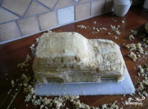 Пришло время доставать торт из холодильника и приводить его в порядок. Теперь берем в руки острый нож и обрезаем лишнее, то есть приближаем форму нашего торта к форме  машины.
