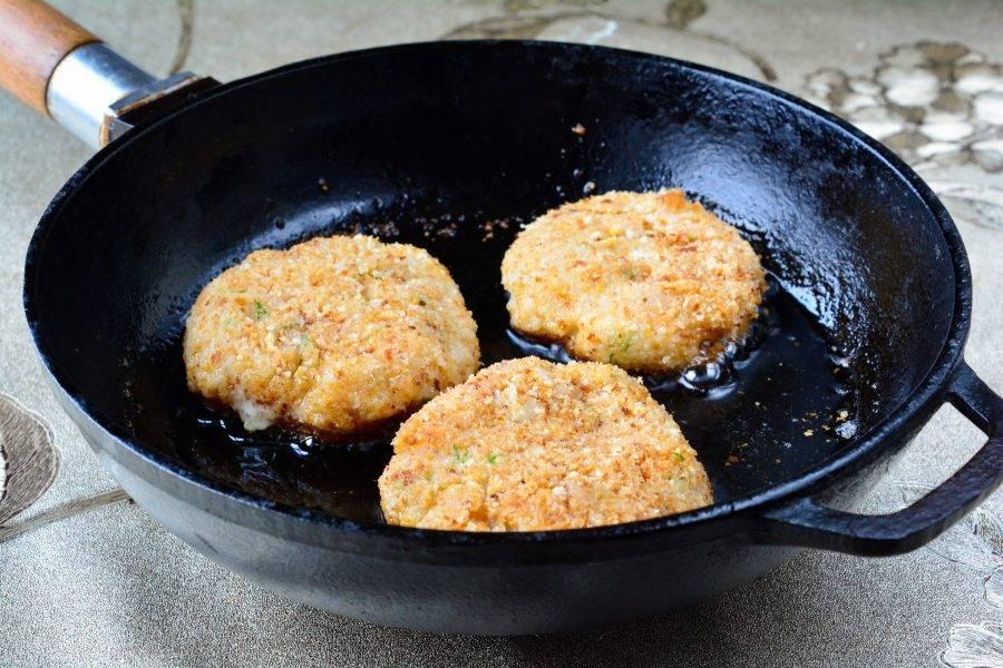 Разогрейте масло на сковороде, выложите котлеты и жарьте на умеренном огне 7-8 минут.