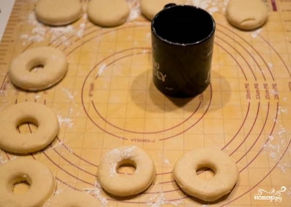 6. Когда тесто готово, поставьте разогреваться масло. Его должно быть довольно много, не менее литра. Тесто разделите на шарики, сделав в центре дырочки.