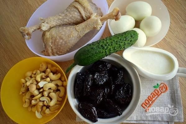 Подготовьте необходимые продукты. Мясо отварите до готовности и остудите. Яйца отварите и очистите от скорлупы. Чернослив залейте горячей водой на 10 минут, откиньте на сито. Если купили уже очищенные орехи, промойте их под водой и просушите.
