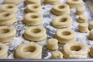 Поставьте разогревать духовку до 200 градусов. На присыпанной мукой поверхности раскатайте тесто в 1,5 см. Вырезайте из него пончики, а потом уложите их на противень, смазанный маслом. Запекайте 20 минут.
