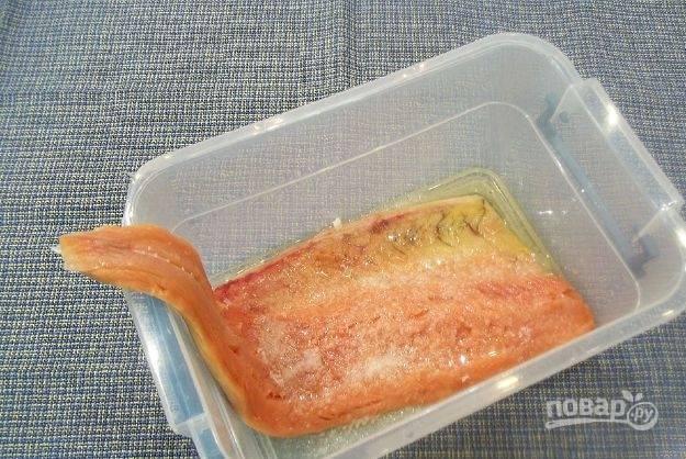 Выложите часть филе. Смажьте его солью с сахаром. Влейте половину масла, равномерно распределите.