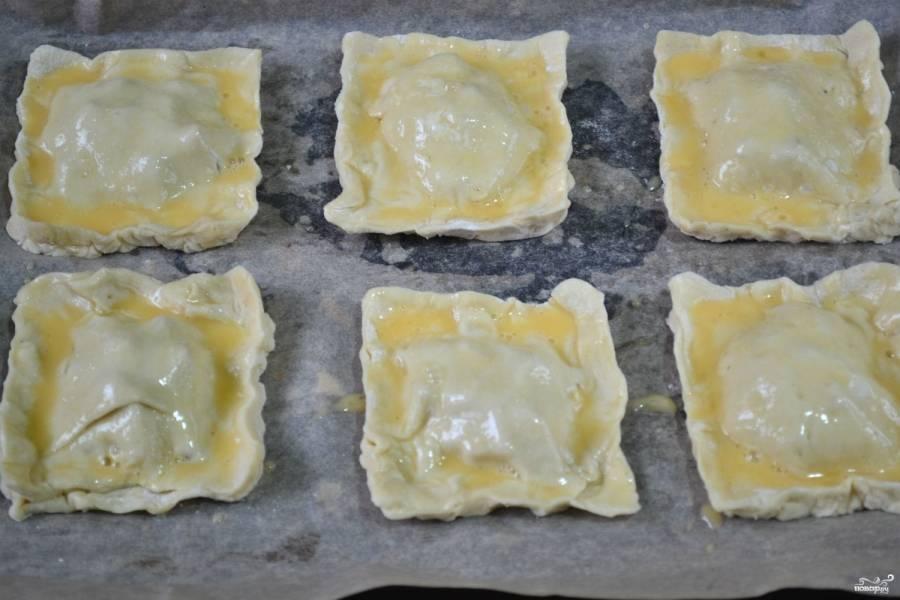 Сверху пирожки смажьте взбитым яйцом, чтобы верх подрумянился. Запекайте слойки в духовке 15-20 минут при температуре 180 градусов.
