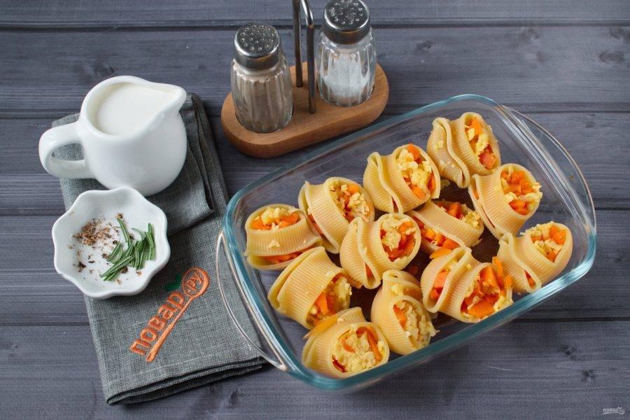 Перемешайте сыр и тыкву, нарезанную кубиками, начините смесью ракушки. Поместите их в форму для запекания.