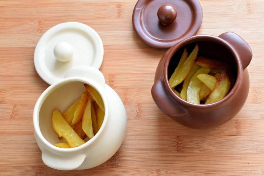 Выложите на дно горшочков по 2-3 горошины черного перца и по лавровому листочку. Выложите картофель.