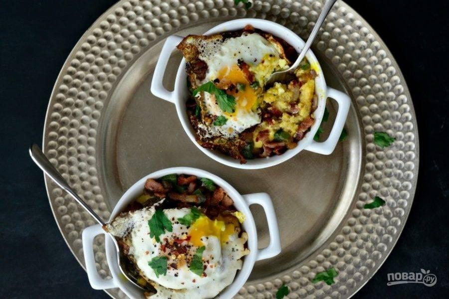 10. Подавайте кашу в чашках, выложив сверху обжаренные овощи с беконом и яйцо. Украсьте блюдо зеленью и красным перцем.