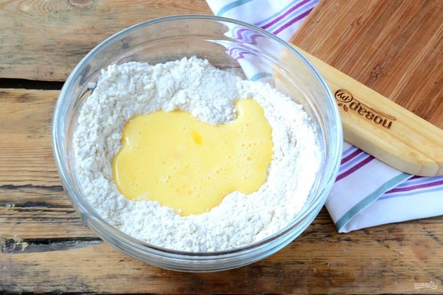 Влейте яичную массу к сухим ингредиентам. Сливочное масло положите в плотный пакет и побейте скалкой, чтобы оно слегка размякло (это по классическому рецепту), но я просто натерла масло на терке.