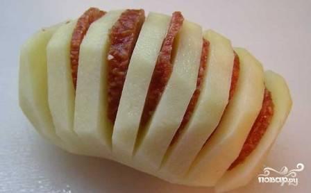 На каждой картофелине сделаем надрезы, в каждый вставляем кусочки колбасы.