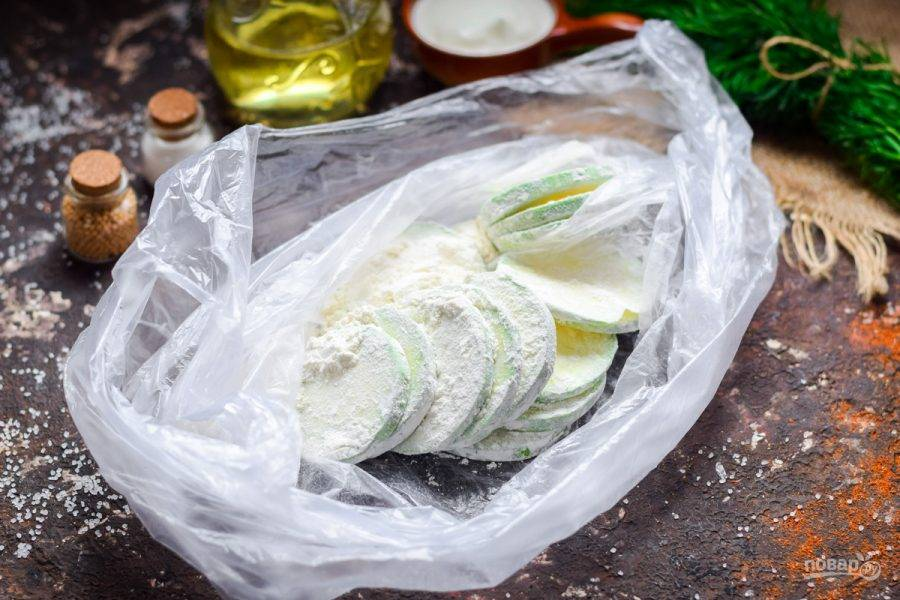 Переложите кабачки в пакет, добавьте немного муки и все перемешайте.