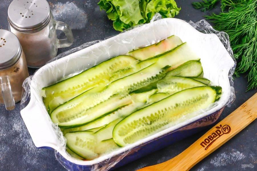 С помощью овощечистки нарежьте огурец, выложите его ленты на слой крабовых палочек.