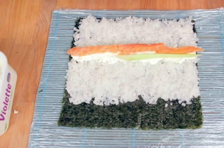 2. На 3/4 листа выложите тонкий слой риса (примерно 0,5 см), после чего выложите на середину риса начинку: нарезанные полосками огурцы, рыбу и авокадо. По желанию выложите полосочку из сливочного сыра.