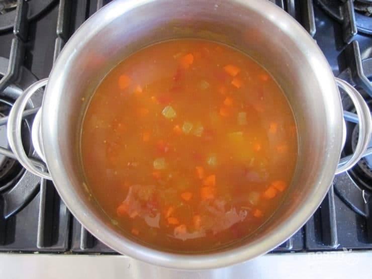 4. Затем влейте бульон. Добавьте мелко нарезанные томаты. Доведите суп до кипения, а потом варите его 15 минут на среднем огне.
