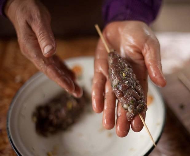 Хорошенько отбейте руками фарш, бросая его в миску, чтобы он стал однородным и липким. На пол часа положите фарш в холодильник. Затем смажьте руки растительным маслом, достаньте фарш и сформируйте из него длинные колбаски, воспользовавшись деревянными палочками.