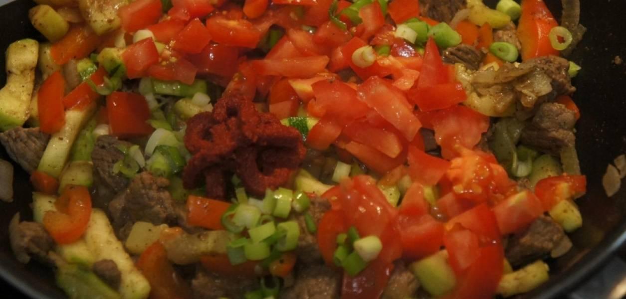 Спустя минут 5-7 - отправляем туда помидоры. Они должны дать сок и превратиться в томатную пасту. Тушим под закрытой крышкой до готовности мяса, полчаса или 40 минут, если надо - добавляйте воды немного. За 5 минут до готовности всыпьте зелень, посолите и поперчите.