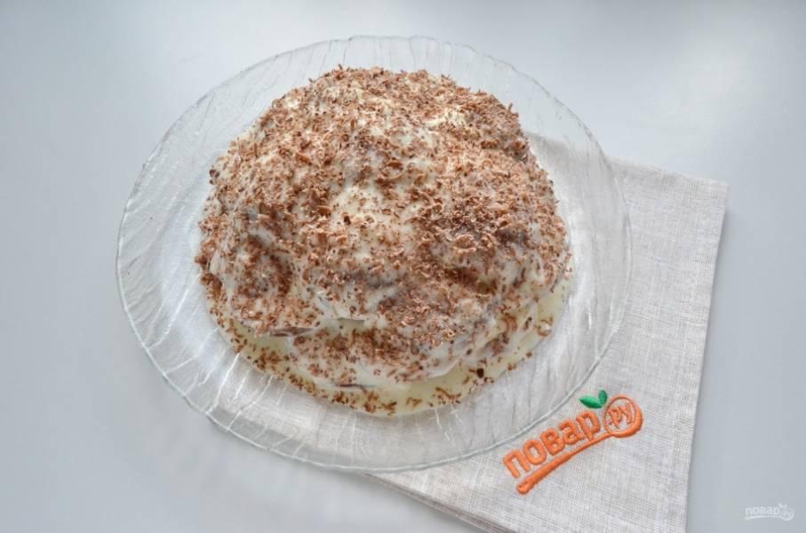 Соберите тортик в виде горки. Несколько половинок я поломала на кусочки, чтобы заполнить пустые места внутри, между пряниками. Сверху щедро смажьте сметанным кремом тортик. Для украшения можно использовать шоколадную глазурь или молотые орехи. У меня был кусочек шоколадки, и я натерла его на мелкую терку над тортиком. Отправьте торт в холодильник на 8-12 часов.