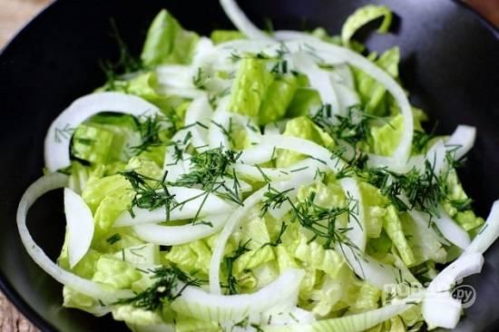 Вымытые и обсушенные листья салата рвем на кусочки и выкладываем на тарелку. Поверх них выкладываем полукольца лука и часть нарезанной зелени укропа.