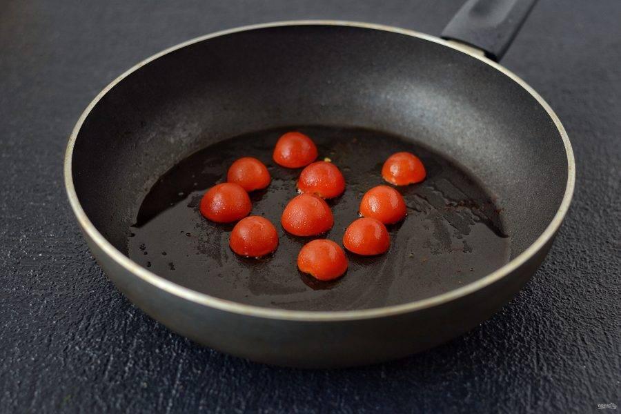Томаты черри разрежьте пополам, затем обжарьте на сковороде.
