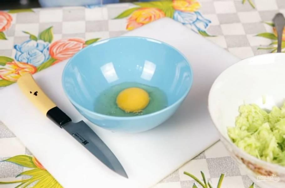 2. Через некоторое время отожмите кабачок руками. Мелко нарежьте чеснок и добавьте к кабачкам. Затем в отдельной миске слегка взбейте вилкой яйцо и добавьте к кабачкам.