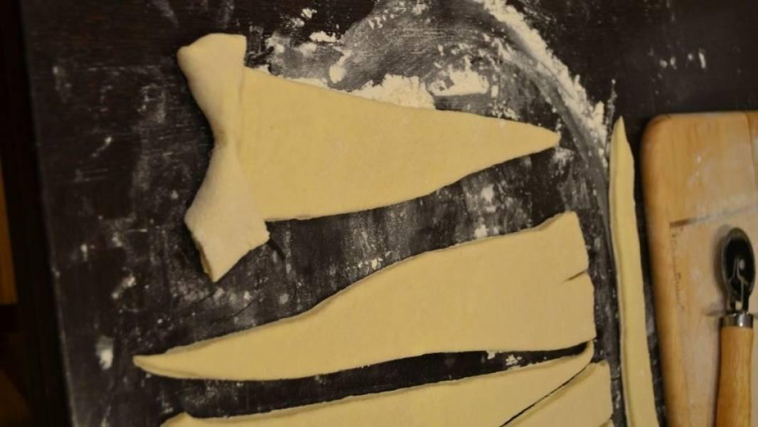 2. С широкой стороны сделайте небольшой разрез, раскройте и заверните в разные стороны. Если в рецепте приготовления круассанов из слоеного бездрожжевого теста используется начинка, то ее следует класть на этот широкий край.