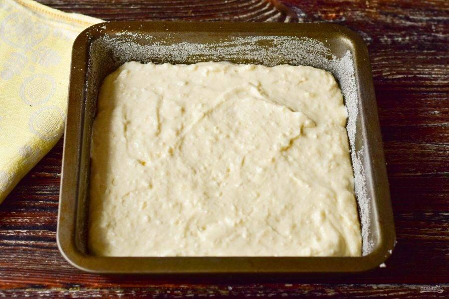 Форму смажьте любым маслом и присыпьте манкой. Выложите творожное тесто, разровняйте его силиконовой лопаткой.