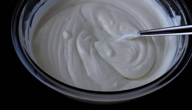 7. Теперь можно заняться кремом. Торт на сметане в домашних условиях будет промазан именно сметанным кремом. Для этого оставшуюся сметану нужно соединить с сахаром и как следует взбить.
