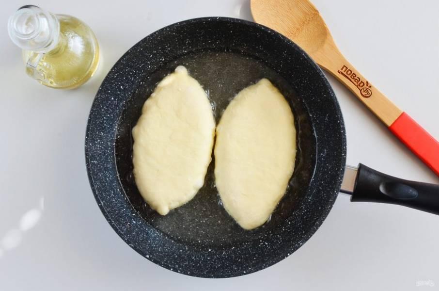 Разогрейте растительное масло, высота масла должна доходить до половины пирожка минимально. В идеале — фритюр. Выложите пирожки и жарьте на среднем огне без крышки.