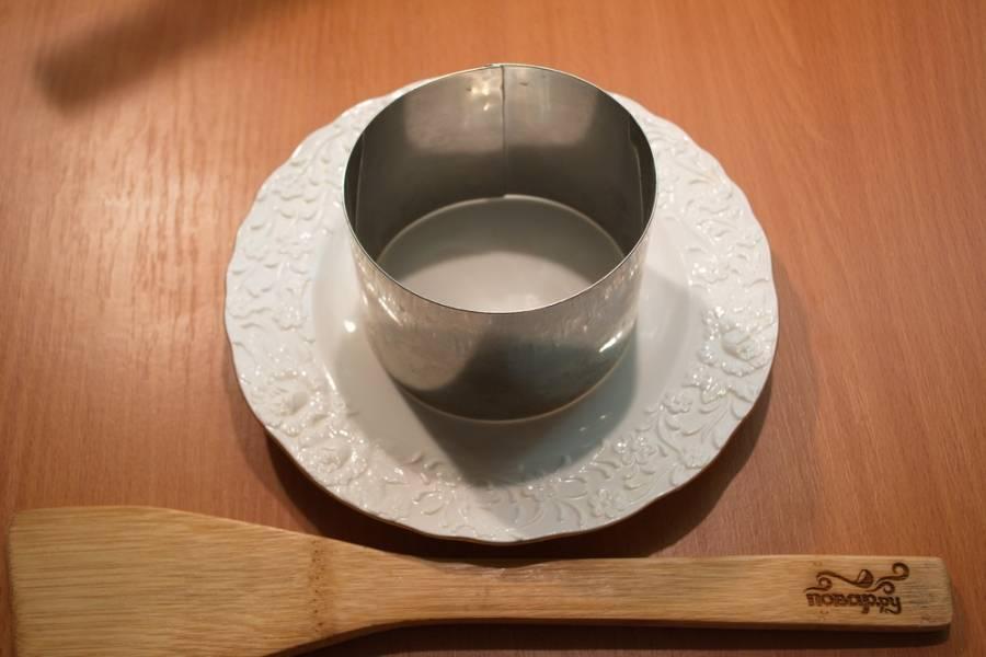 Возьмите плоское блюдо или тарелку. Установите на нее сервировочное кольцо. Вместо кольца можно использовать широкую пластиковую бутылку, вырезав из нее высокое кольцо.