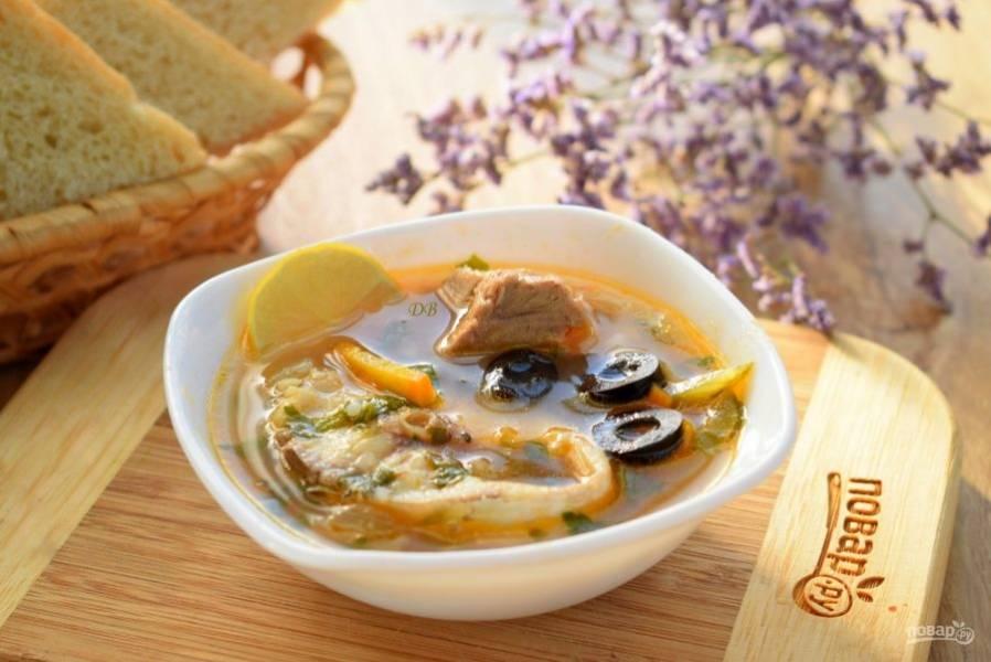 Соедините с бульоном, добавьте измельченную зелень, посолите по вкусу. Накройте крышкой, снимите с огня, дайте настояться в течение нескольких минут. Подавайте солянку с тунцом с ломтиком лимона и нарезанными маслинами. Приятного аппетита!