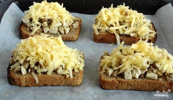 Противень застилаем пергаментной бумагой. Выкладываем на противень кусочки хлеба, на хлеб выкладываем грибную начинку, сверху присыпаем тертым сыром.