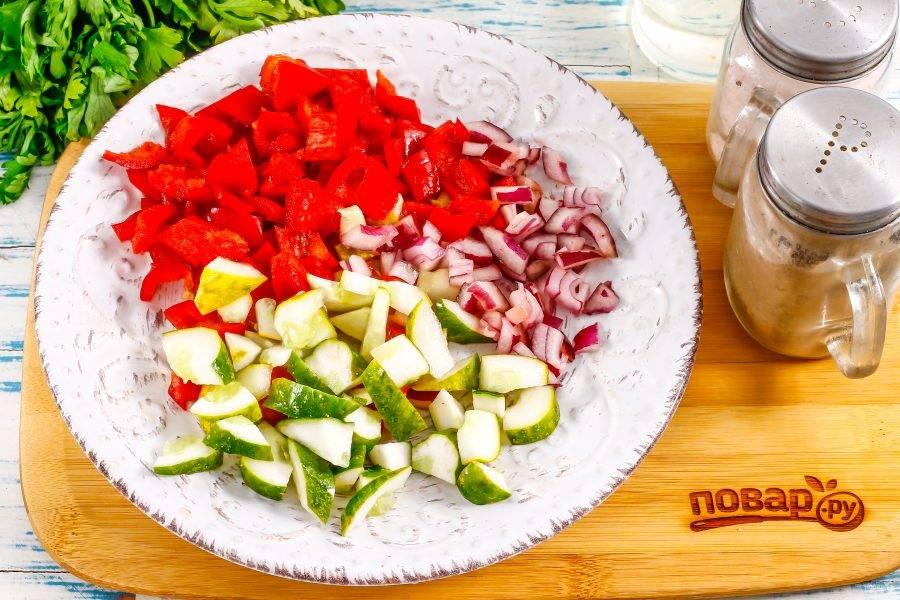 Очистите болгарский перец от семян, срезав крышечку, промойте в воде. Огурцы промойте, удаляя шипы с их поверхности, срежьте хвостики. Очистите от кожуры лук и промойте. Нарежьте все овощи кубиками.