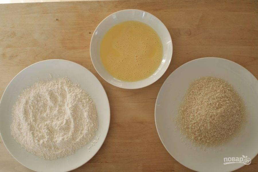 В трех отдельных мисочках подготовьте панировку. В первую емкость выложите муку, перемешанную с солью и перцем, во второй взбейте яйца. В третью выложите панировочные сухари.