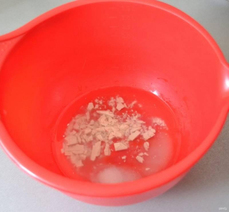 В емкость для замешивания теста влейте теплую воду, добавьте дрожжи, соль, сахар, 1 столовую ложку растительного масла, размешайте, дайте дрожжам активироваться 15-20 минут.